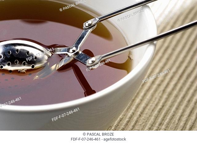 Close-up of a bowl of tea with a sieve