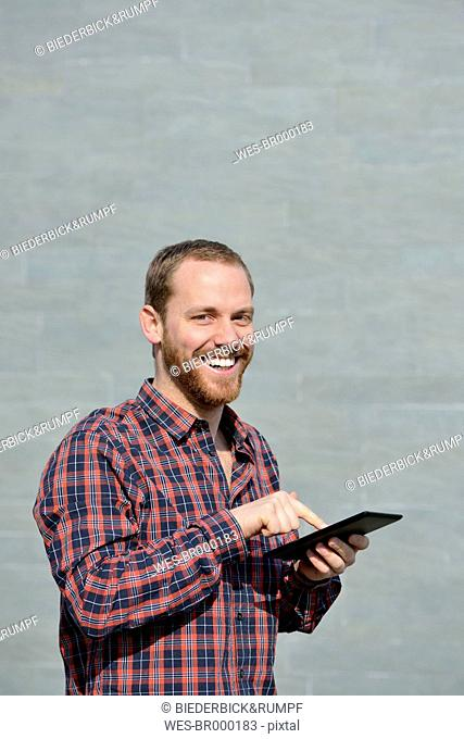 Portrait of smiling young man with mini tablet