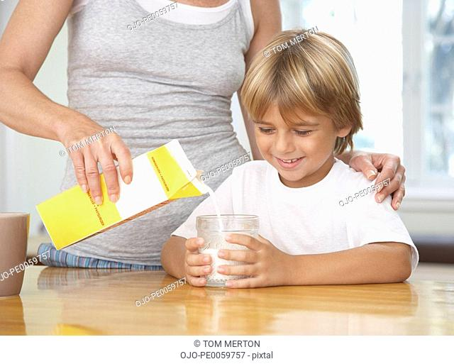 Woman in kitchen pouring young boy glass of milk