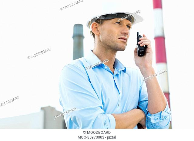 Male architect communicating on walkie-talkie at site