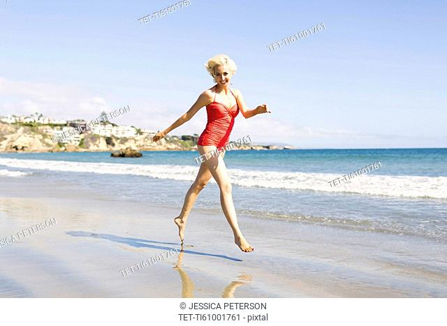 Blond woman running on beach