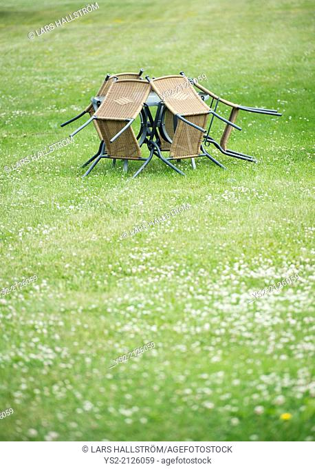 Empty garden patio with vacant chairs and table on big lawn with copy space