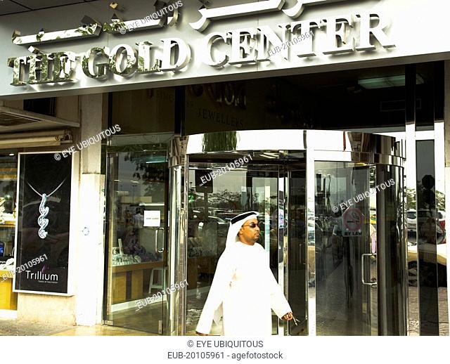 Emirati Arab man in Dishdasha passes Gold Center at Gold Souk Deira