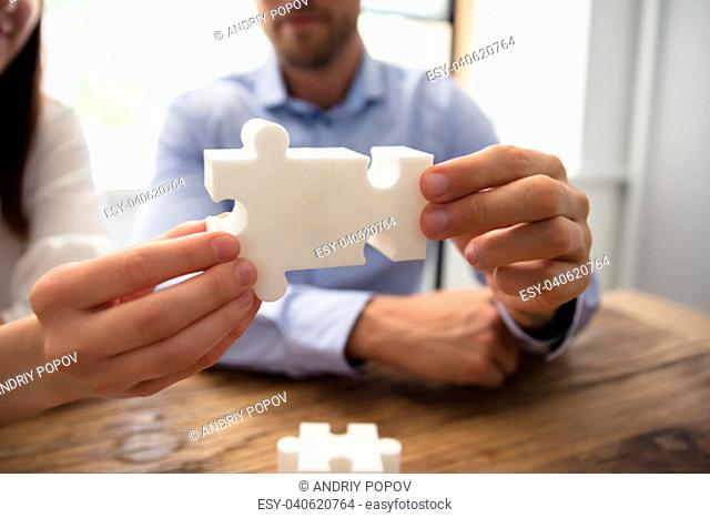 Close-up Of Two Businesspeople White Jigsaw Pieces Over Wooden Desk