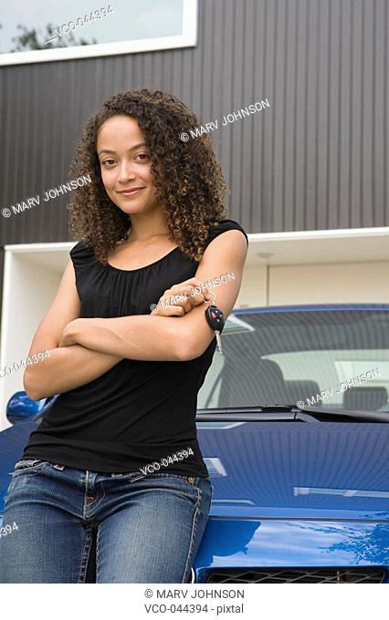 Smiling woman with car keys leaning on car in driveway