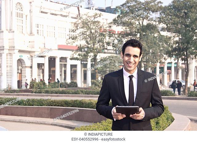Portrait of a businessman holding a digital tablet , INDIA , DELHI