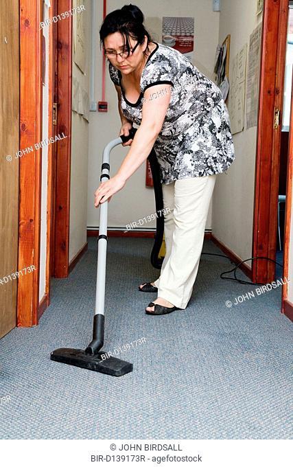 Eastern European working as cleaner hoovering office corridor
