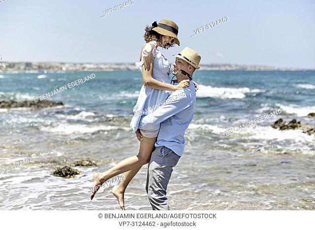 man carrying woman at beach, love, couple, dating, honeymoon, in Hersonissos, Crete, Greece