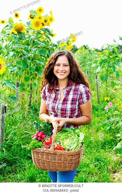 Portrait of young woman holding basket of fresh vegetables in allotment