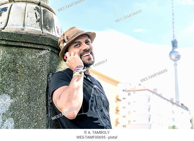 Germany, Berlin, portrait of smiling man on the phone with television tower in the background