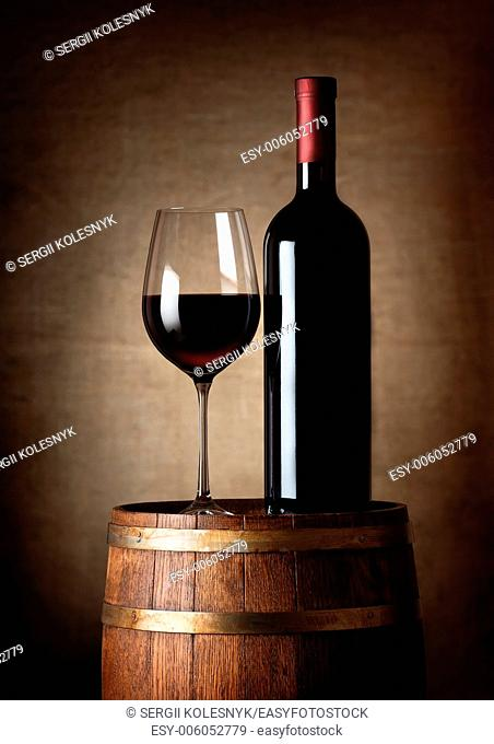 Wine standing on a barrel on a background of a canvas