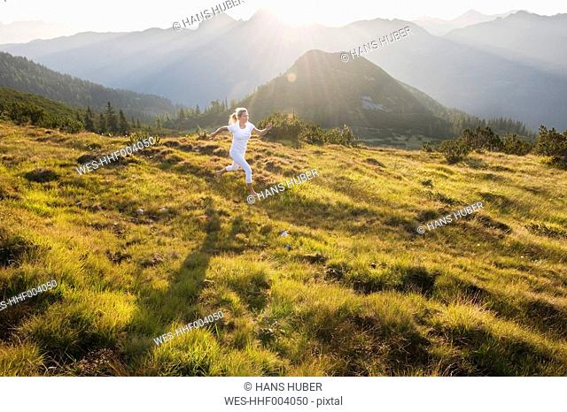Austria, Salzburg County, Young woman running in alpine meadow
