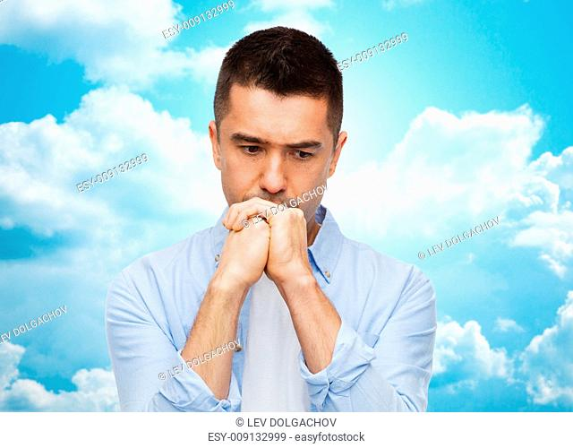 sadness, problem, sorrow and people concept - unhappy man thinking over blue sky with clouds background