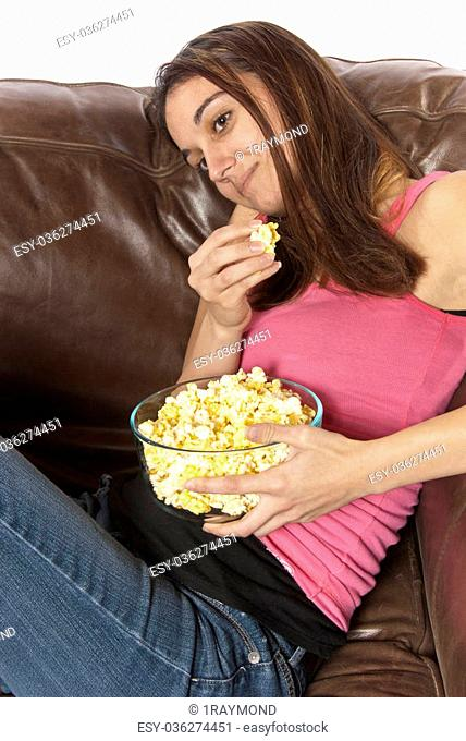 Young woman sits in a leather chair relaxing and eating popcorn. Head laying on back of couch. This could be retro of the house wife at home watching a soap...