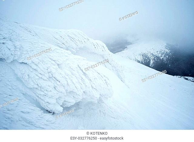 Hoarfrost on a rock in the mountains. Winter landscape a cloudy day. Severe weather