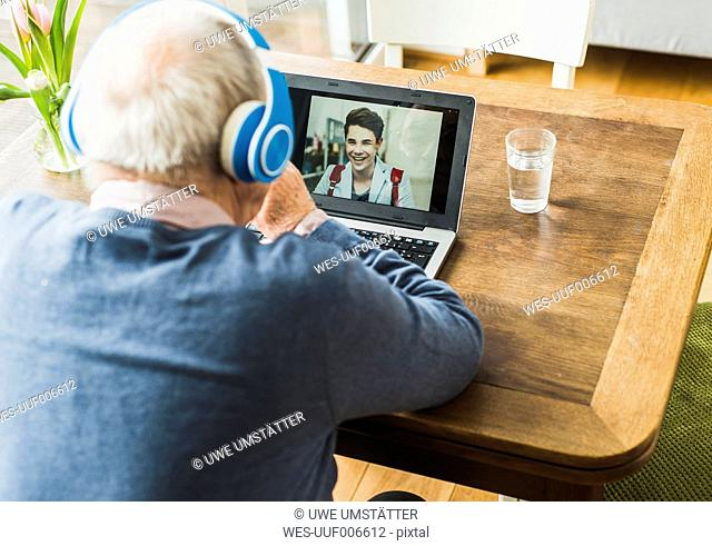 Senior man using laptop and headphones for skyping with his grandson