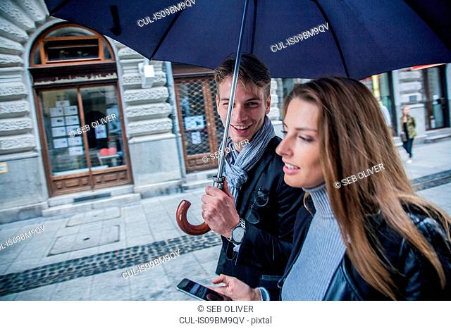 Couple with umbrella on morning commute, Budapest, Hungary