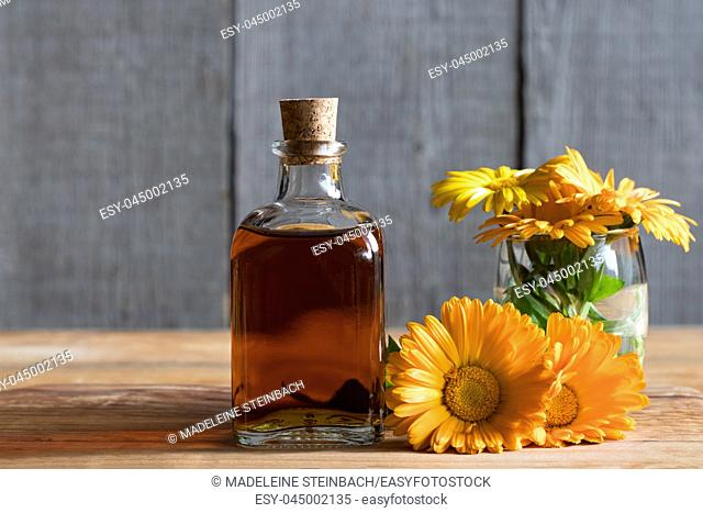A bottle of calendula (marigold) tincture with fresh calendula flowers