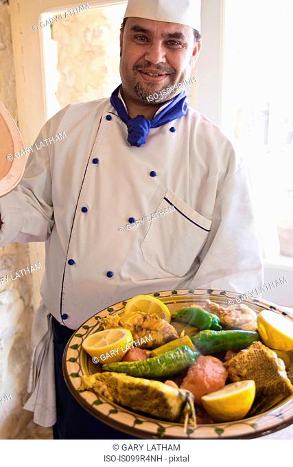 Chef with fish and vegetable dish in Djerba, Tunisia