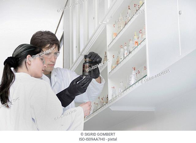 Chemistry students looking at container in lab
