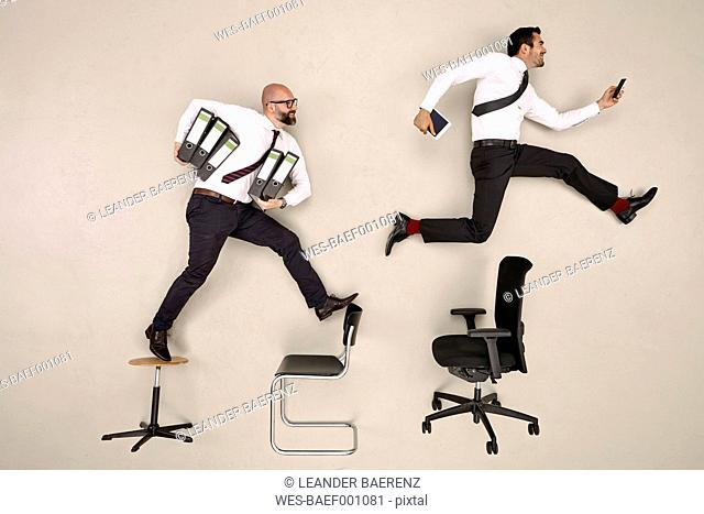 Businessmen jumping over chairs carrying folders and devices