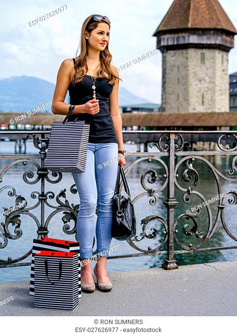 Photo of a beautiful young woman standing with shopping bags, in Luzern Switzerland.
