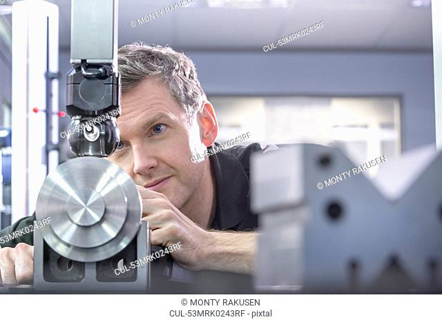 Worker using machinery in factory