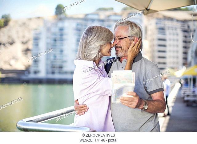 Senior couple taking a city break, holding map