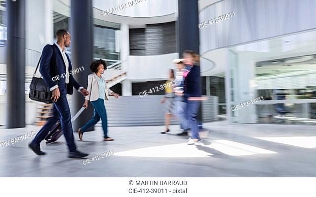 Business people walking, pulling suitcase in modern office lobby