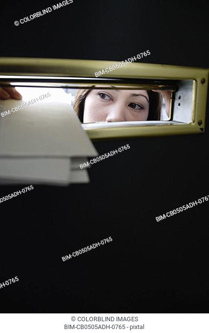 Woman putting mail through slot