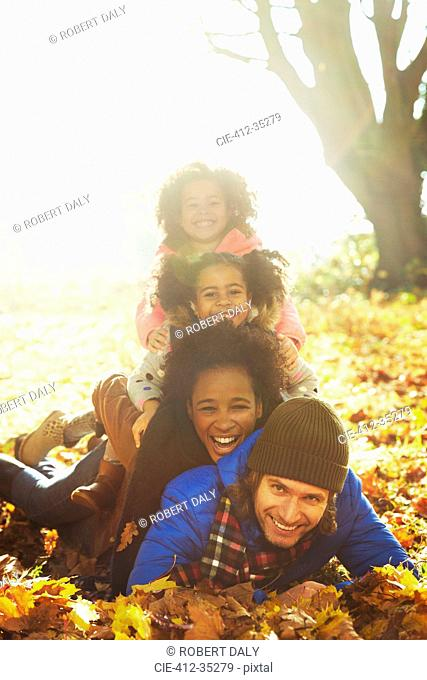 Portrait smiling young family laying on top of each other in sunny autumn leaves