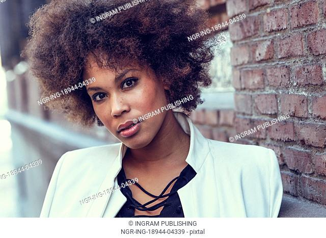 Close-up portrait of black woman with afro hairstyle standing in urban background. Mixed girl wearing white jacket and black dress posing near a brick wall