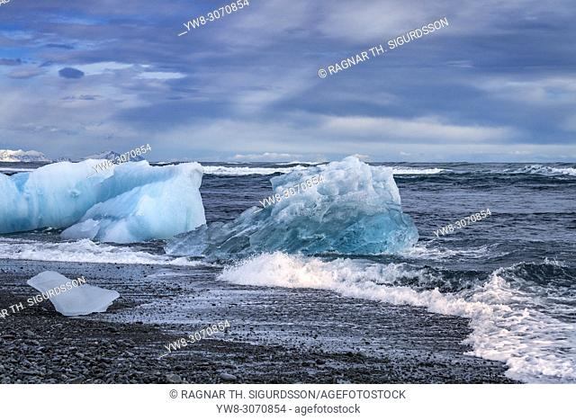 Glacial ice on a black sand beach, Breidamerkurfjara beach, Vatnajokull Ice Cap, Iceland. Large chucks of ice calve off of the Breidamerkurjokull and then wash...