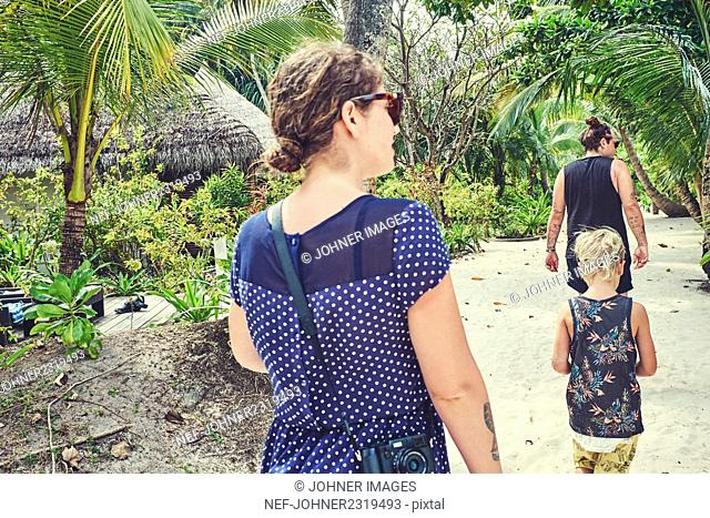 Family walking under palm trees