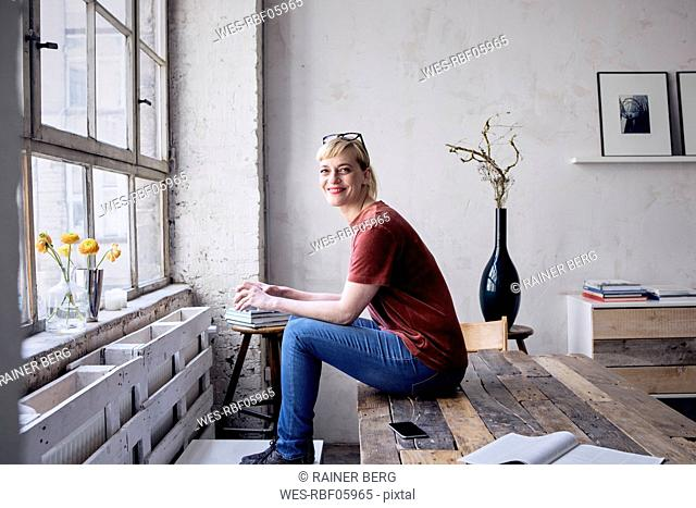 Portrait of smiling woman with coffee mug sitting on desk in loft