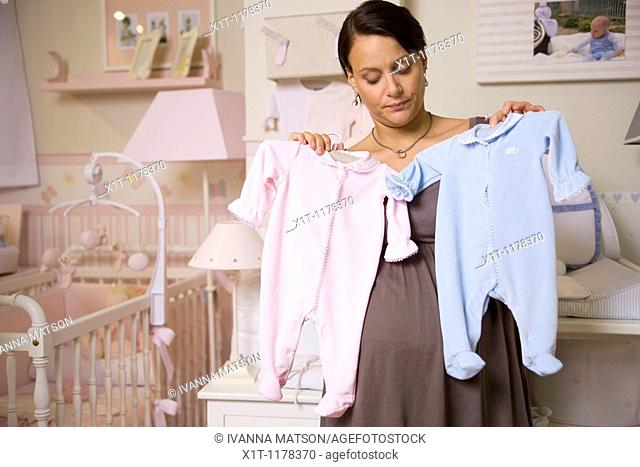 Pregnant woman with baby clothes