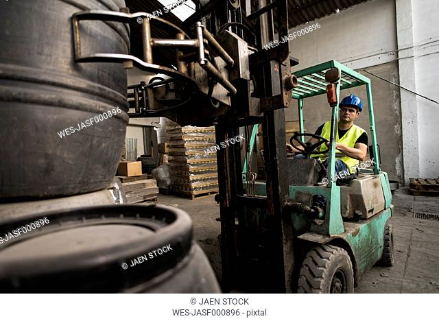 Worker inside cabin lift machine, barrels