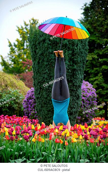 Woman with umbrella doing headstand