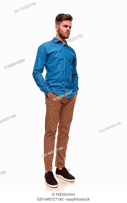 serious young casual man standing on white background looks to side, full length picture