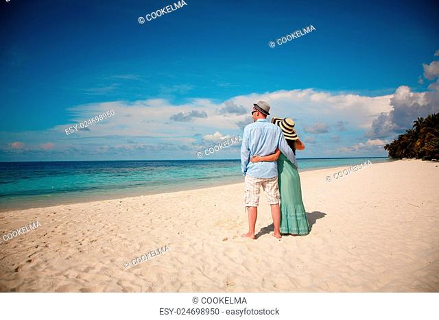 Couple on vacation walking on a tropical beach Maldives. Man and woman romantic walk on the beach