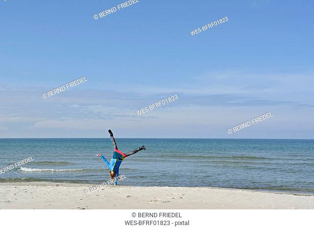 Germany, Pomerania, Hiddensee, girl doing handstand on the beach