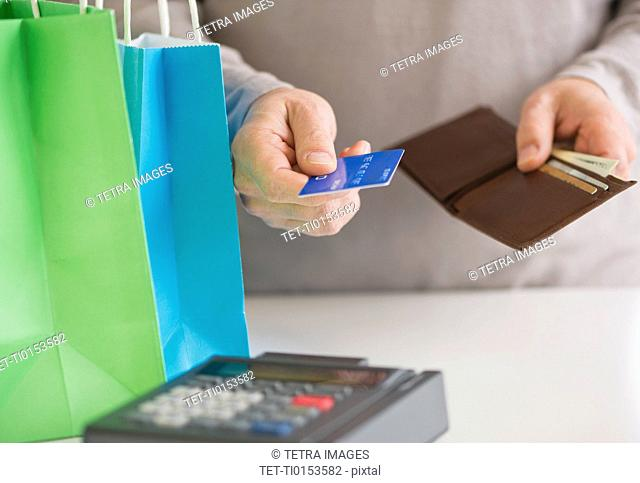 Close up of man's hands holding credit card and wallet, studio shot