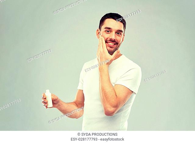 beauty, skin care, body care and people concept - smiling young man applying cream or lotion to face over gray background