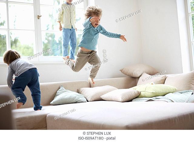 Three young boys jumping on sofa
