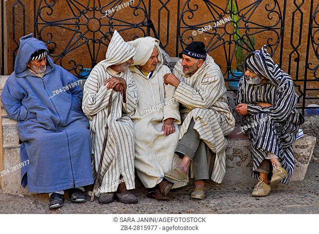 Old local men dressed with chilabas or djellabas (bereber clothes) at the heart of the central square, Outa el Hammam, Chefchaouen or Chaouen, Rif Region