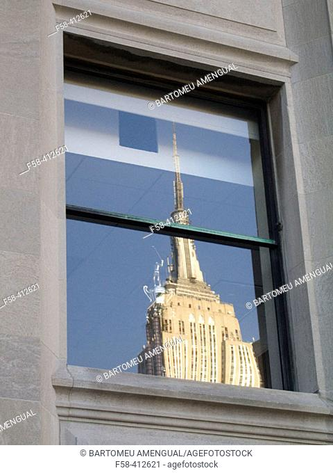 Empire State building reflected on window. New York City, USA