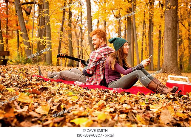 Young couple back to back on picnic blanket in autumn forest