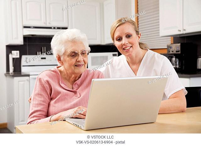 Nurse helping senior woman with laptop