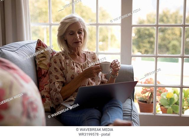Senior woman having coffee while using laptop on the sofa