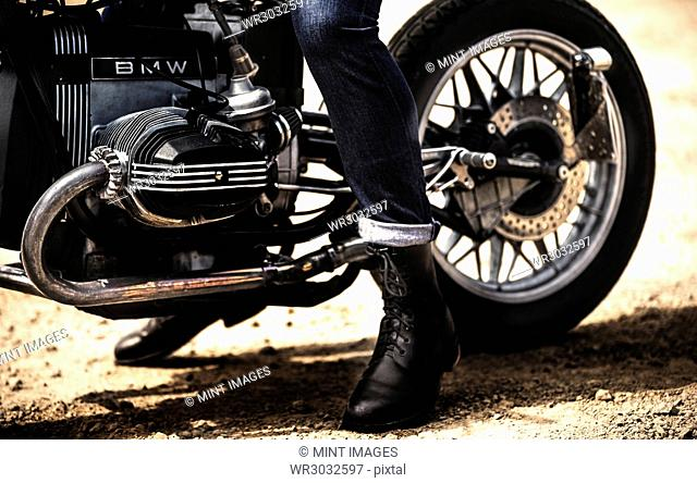 Low section view of man wearing jeans and black leather boots sitting on cafe racer motorcycle